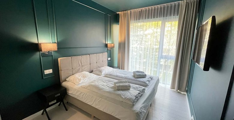 Apartament frontowy B2.17 z dwiema sypialniami z widokiem na wydmy, drzewa i częściowym na morze