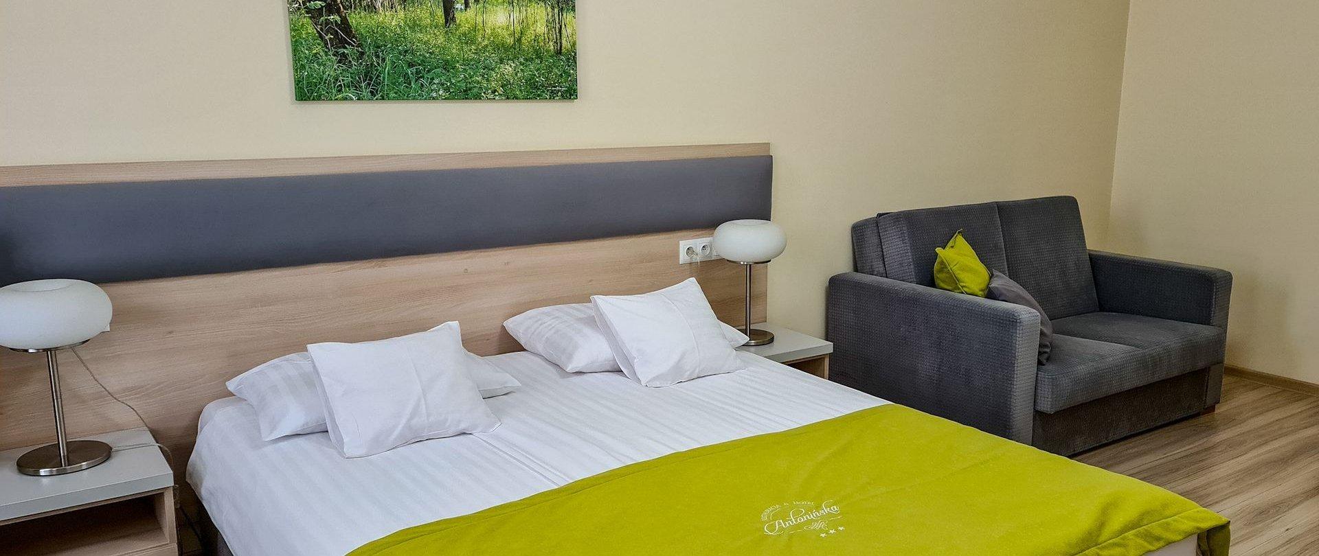 Przestronny pokój z łóżkiem małżeńskim i sofą w drugim budynku hotelowym